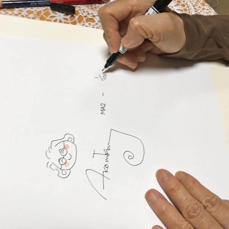 裏面には作家本人による直筆のサイン(作家の顔入り)が入っています。